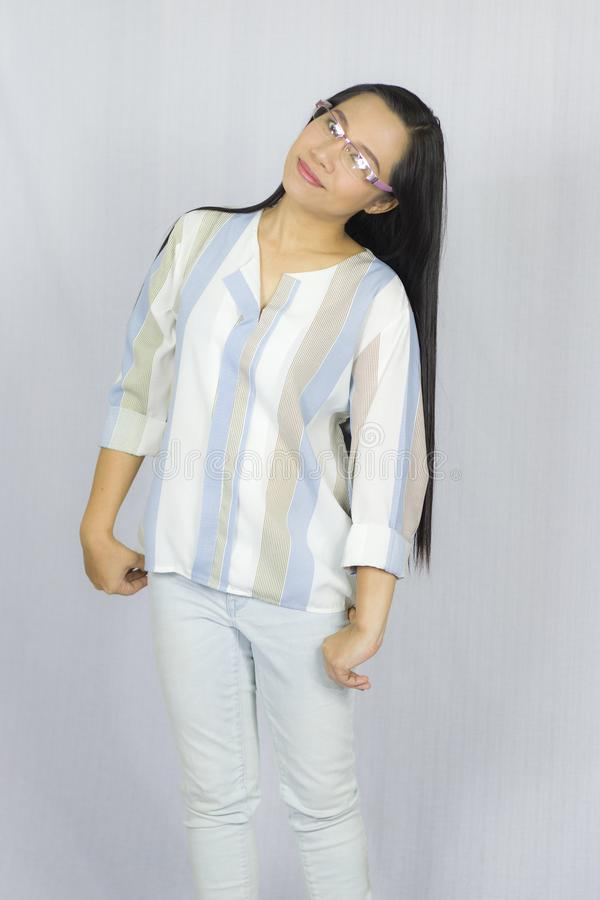 Rolig asiatisk kvinna i exponeringsglas som poserar lyckligt leende som isoleras p? gr? bakgrund arkivbild