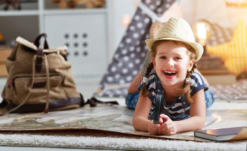 Rolig barnflickaturist med världskartan, ryggsäcken och förstoringsapparaten royaltyfri bild