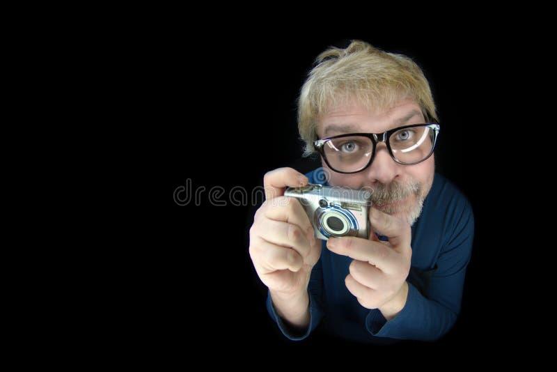 Rolig blond manhåll en tappningkamera och peka den på kameran - som isoleras på svart royaltyfri bild