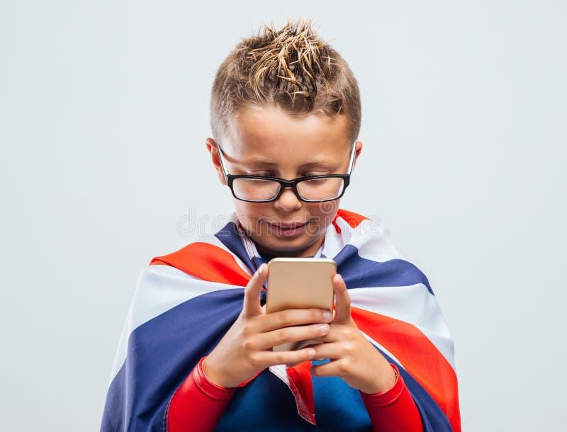 Rolig brittisk superhero som använder en smart telefon arkivbilder