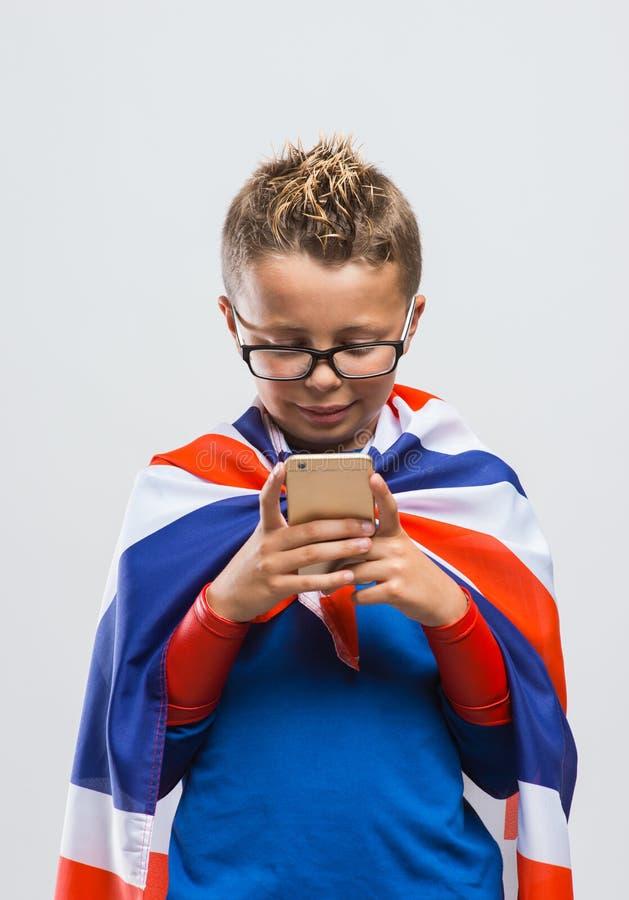 Rolig brittisk superhero som använder en smart telefon arkivfoto