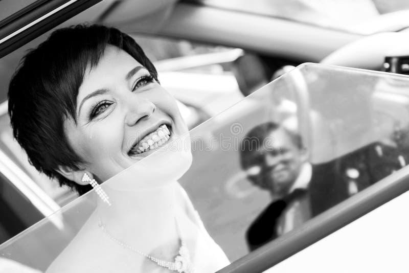 Rolig brud i bilen som ler brudgummen Kvinna 35 år bröllop fotografering för bildbyråer