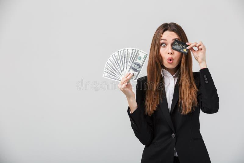 Rolig dam som grimacing och rymmer kassa och kreditkorten i händer royaltyfri foto