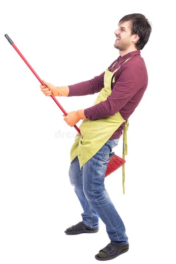 Rolig driftig ung man som spelar med kvasten under cleaninen arkivfoto