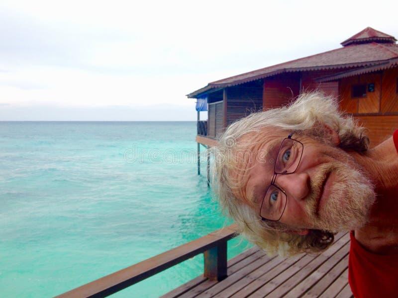 Rolig enfaldig äldre hög man med exponeringsglas som photobombing tropiskt öferiekort royaltyfria bilder
