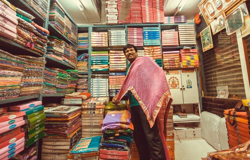 Rolig försäljaredanandepresentation inom litet textillager med klänningar och halsdukar arkivbilder