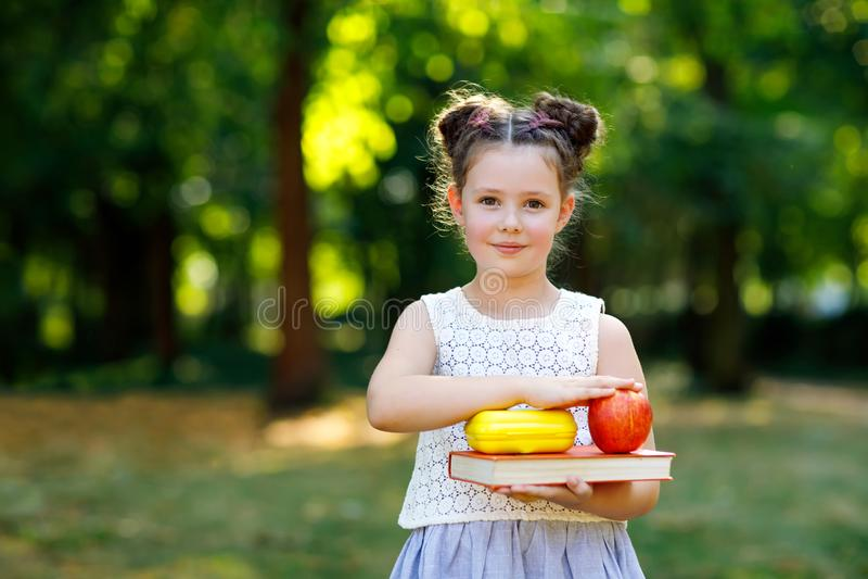 Rolig förtjusande flicka för liten unge med boken, äpplet och ryggsäcken på den första dagen till skolan eller barnkammaren Barn  arkivbilder