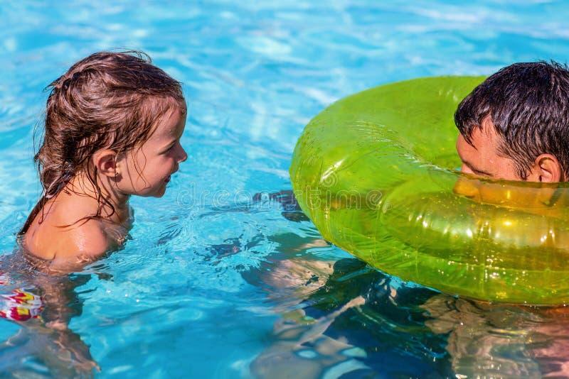 Rolig fader och dotter som spelar i simbassäng f?r sommarterritorium f?r katya krasnodar semester royaltyfri foto