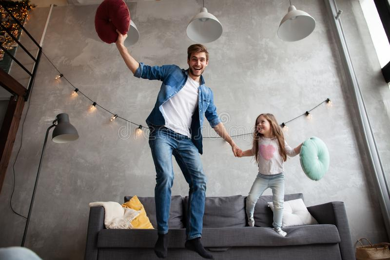 Rolig fader och gullig ungedotter som skrattar banhoppningen som har gyckel i vardagsrum, aktiv familj som tycker om rörande spel royaltyfria foton