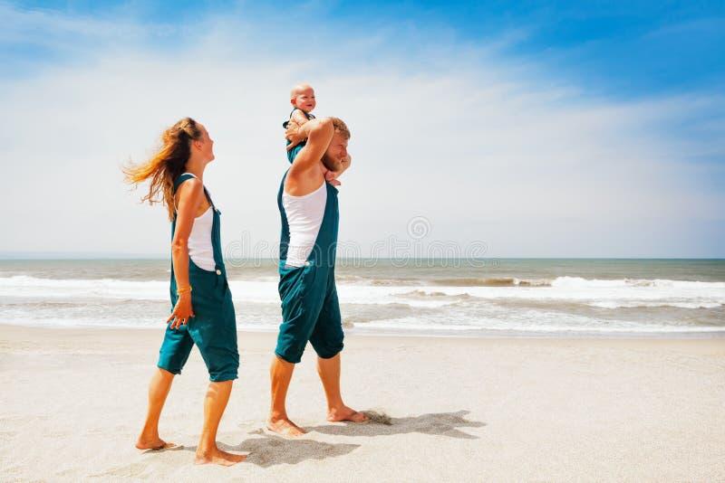 Rolig familj som går på havsstranden royaltyfri foto