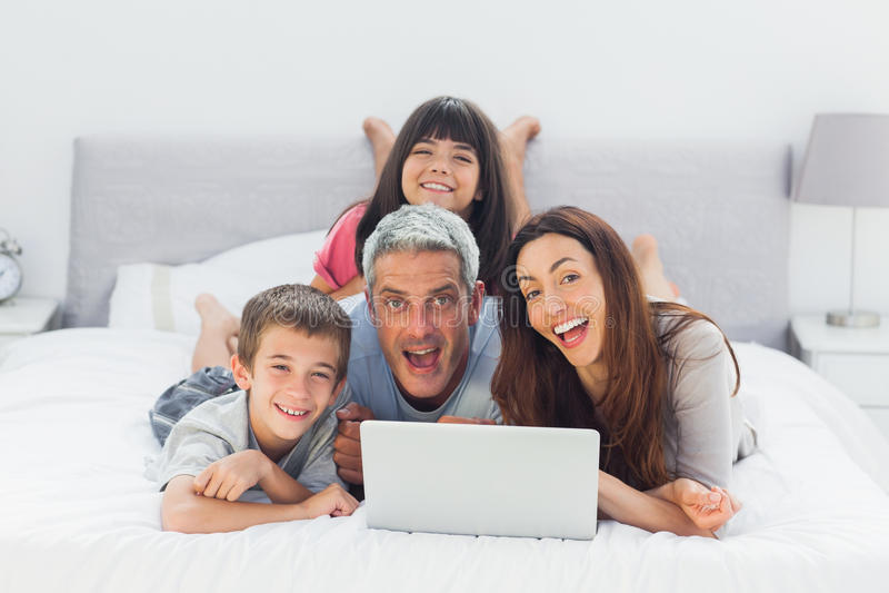 Rolig familj som ligger på säng genom att använda deras bärbar dator arkivbild