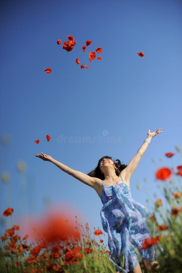 rolig flicka för fält som har banhoppningvallmor arkivbild