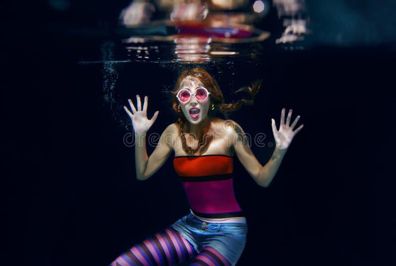Rolig flicka för rött hår på den undervattens- mörka bakgrunden royaltyfria bilder