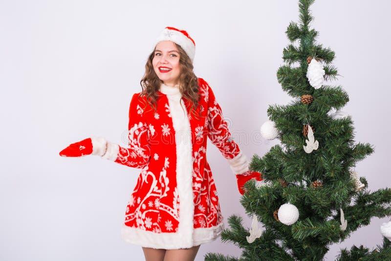 Rolig flicka, i att bära dräkten för xmas santa nära julträd Ferier, gyckel och folkbegrepp fotografering för bildbyråer