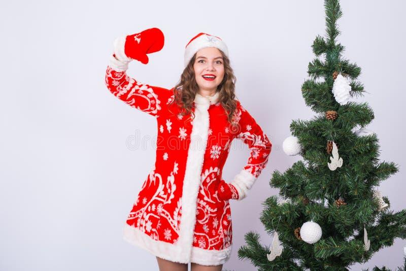 Rolig flicka, i att bära dräkten för xmas santa nära julträd Ferier, gyckel och folkbegrepp arkivfoto