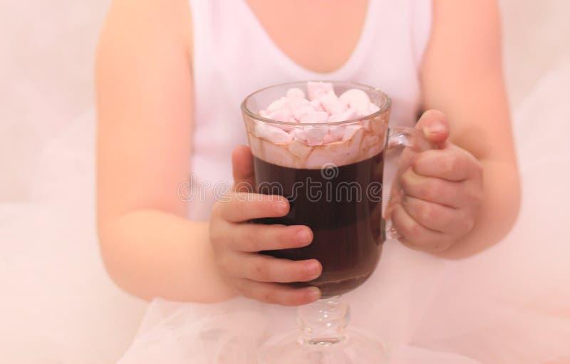 rolig flicka i ballerinaballerinakjol med ett exponeringsglas av den varma drinken i hennes händer royaltyfria bilder