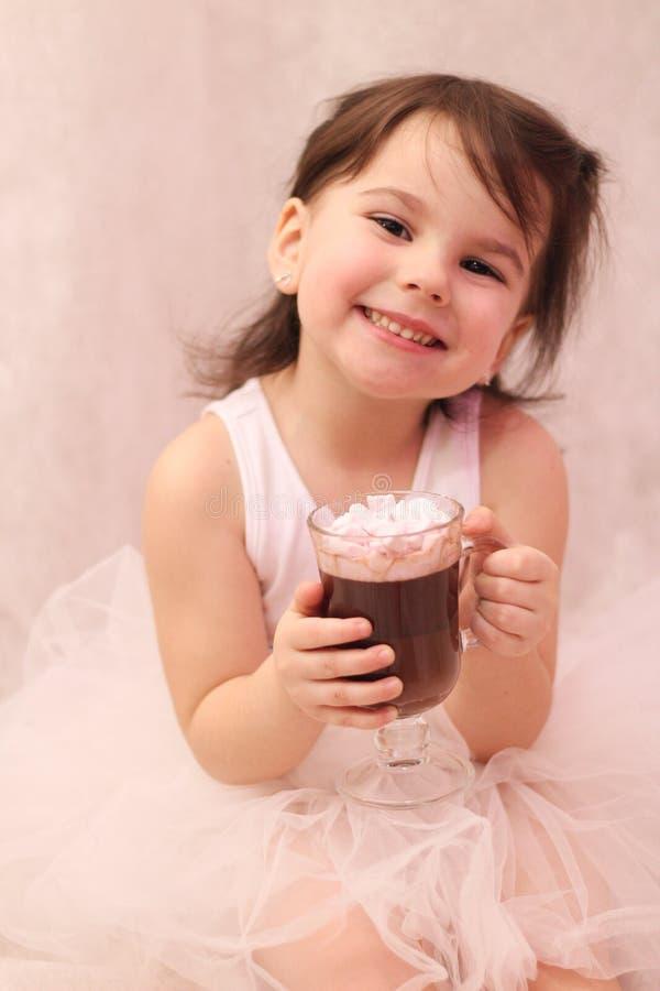 rolig flicka i ballerinaballerinakjol med ett exponeringsglas av den varma drinken i hennes händer arkivbilder