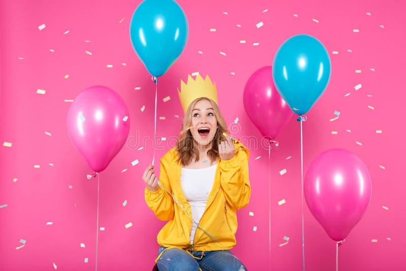 Rolig flicka i födelsedaghatt, ballonger och flygkonfettier på bakgrund för pastellfärgade rosa färger Attraktiv tonåring som fir royaltyfri bild