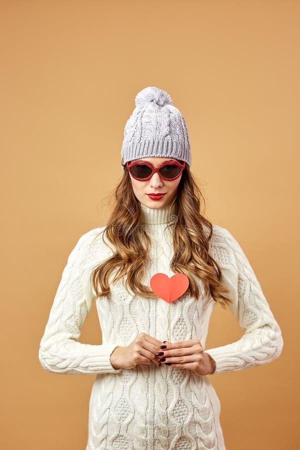 Rolig flicka i solglasögon de rikagyckel för iklädd vit stucken tröja och hattmed en röd pappers- hjärta på en pinne på en beiga arkivbilder