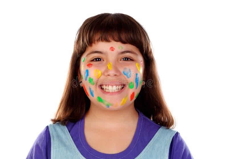 Rolig flicka med framsidan som är full av målarfärg fotografering för bildbyråer