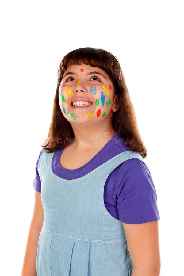 Rolig flicka med framsidan som är full av målarfärg arkivfoto
