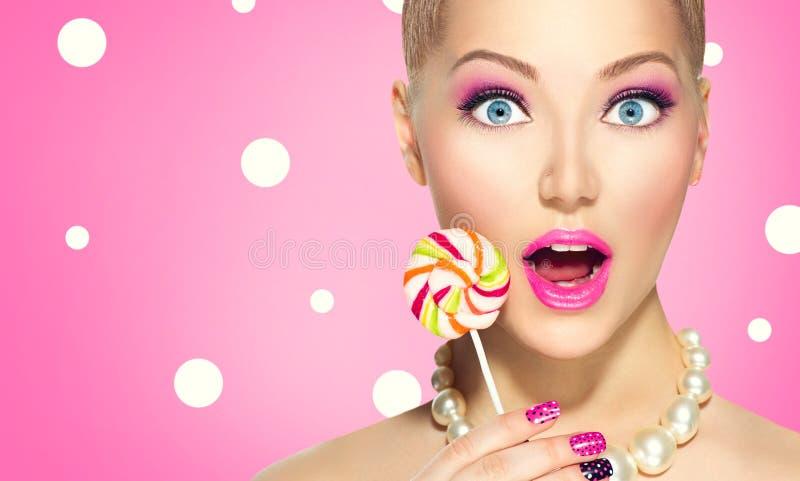 Rolig flicka som äter klubban arkivfoton