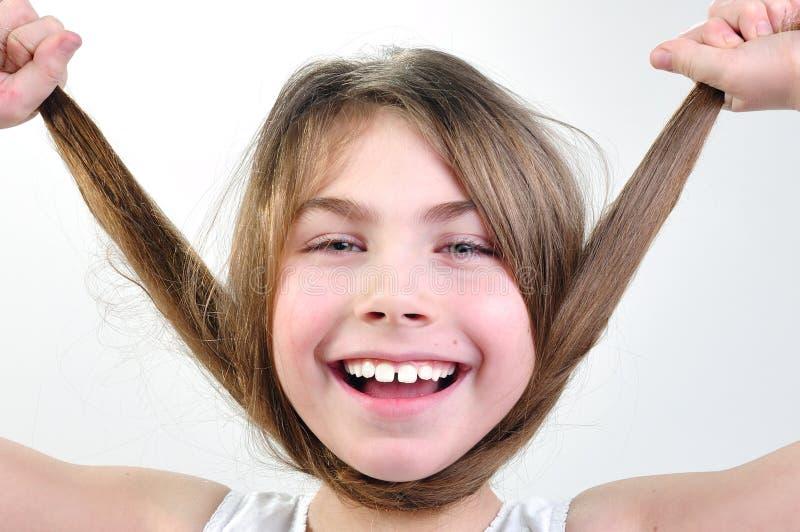 Rolig flicka som leker med henne hår arkivbilder
