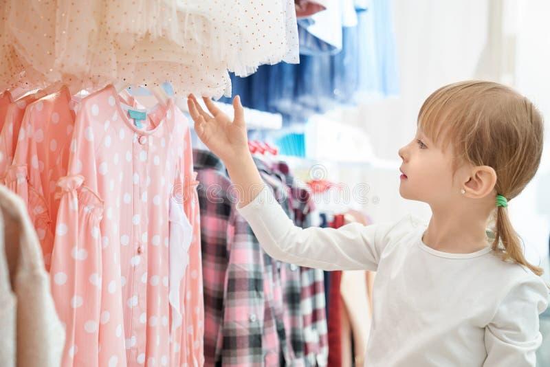 Rolig flicka som ser den älskvärda rosa klänningen i lager royaltyfria bilder