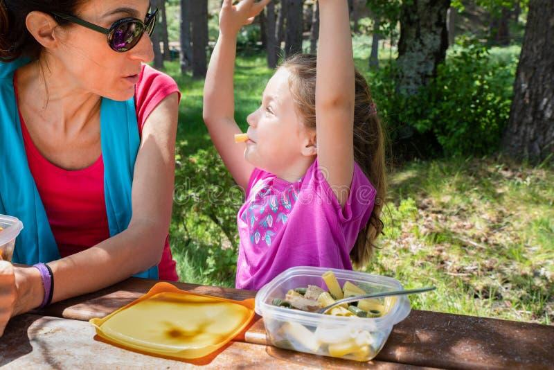 Rolig flicka som spelar med makaroni i hennes mun som ser hennes moder som äter från en plast- lunchbox i en tabellpicknick i lan royaltyfri bild