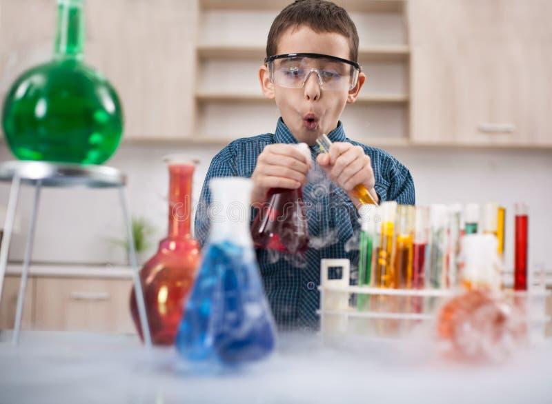 Rolig forskarepojke som arbetar i ett laboratorium royaltyfri foto