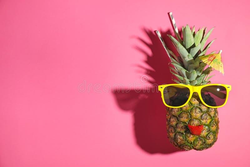 Rolig framsida som göras av ananas, solglasögon och jordgubbeskiva med coctailparaplyet på rosa bakgrund Utrymme f?r text arkivbild