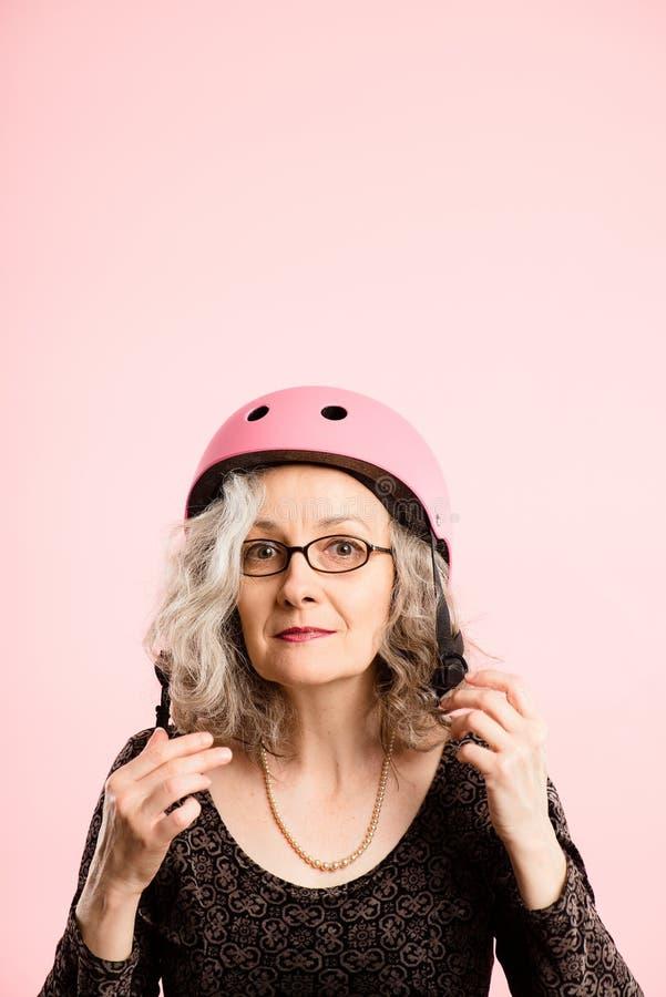 Rolig kvinna som ha på sig verklig cykla rosa bakgrund för hjälmstående arkivfoton