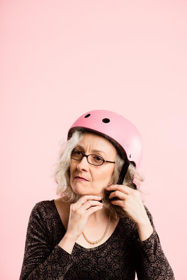 Rolig kvinna som ha på sig verklig cykla rosa bakgrund för hjälmstående arkivbild