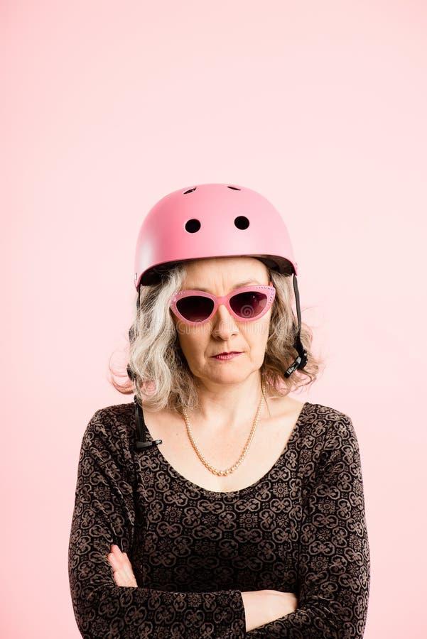 Rolig kvinna som ha på sig verklig cykla rosa bakgrund för hjälmstående royaltyfri fotografi