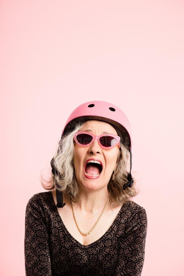 Rolig kvinna som ha på sig verklig cykla rosa bakgrund för hjälmstående fotografering för bildbyråer