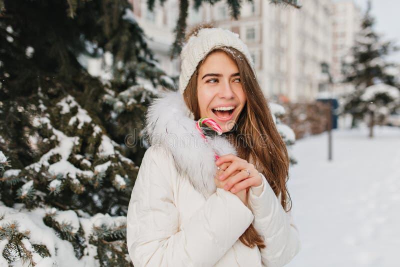 Rolig glad vinterflicka med lollypop i stad Ha gyckel runt om snö, galet lynne och att le, positiva brightful sinnesrörelser royaltyfria bilder