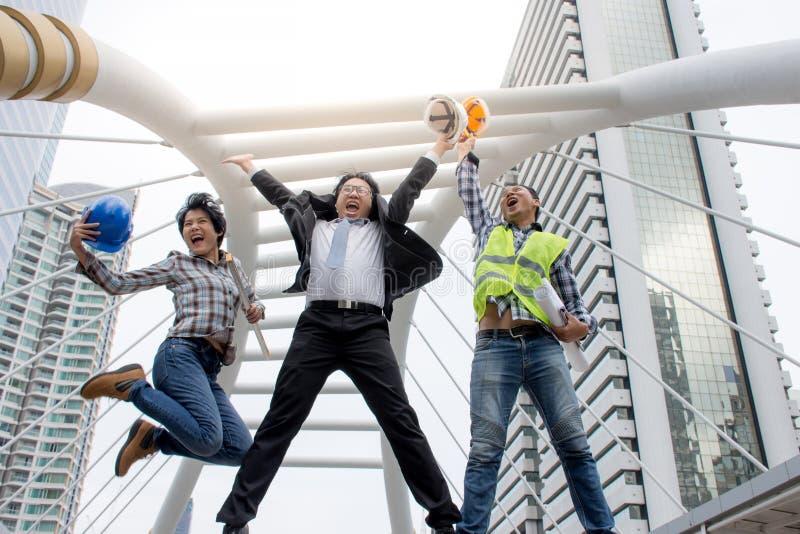 Rolig gladlynt affärsman och teknikerer som hoppar i luft och lyfter armar med jobb till framgång royaltyfri foto