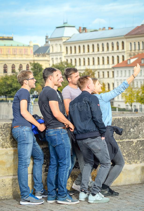 Rolig grupp av grabbturister som tar selfie på den Charles bron, Prague, Tjeckien royaltyfri fotografi