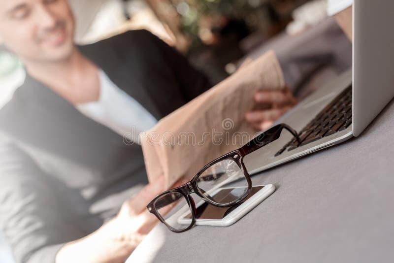 rolig guinealunch för bakgrund över white för pigståendetid Ung man i dräkten som sitter på kafét på slut för glasögon och för te arkivbild