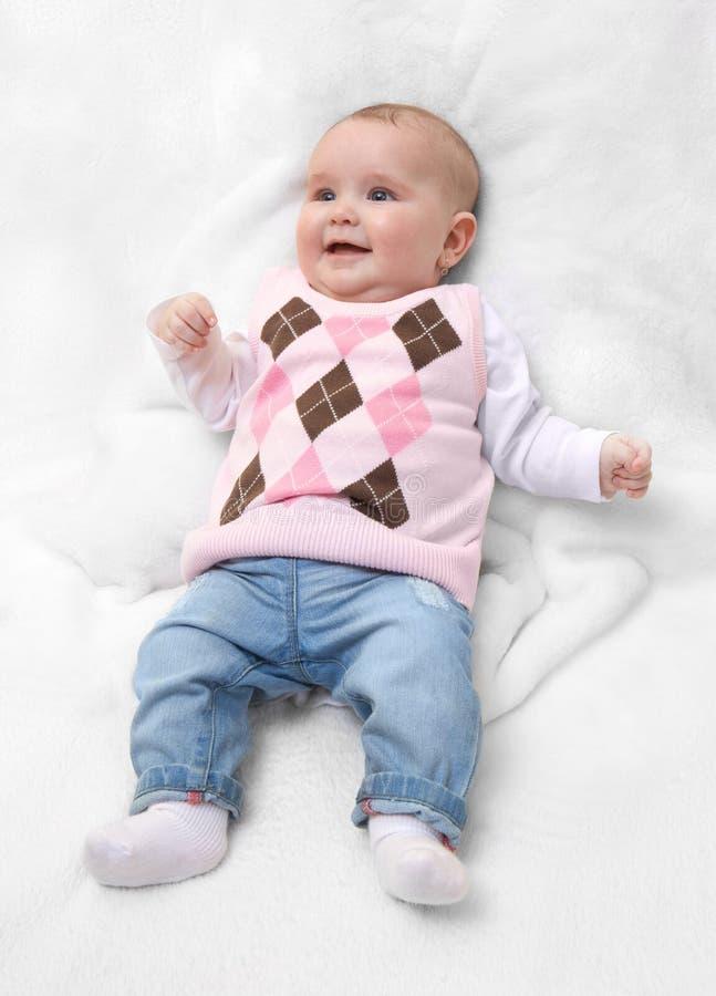 Rolig gullig kvinnlig nyfödd iklädd rosa tröja och jeans på den vita pälsfilten Spädbarnet behandla som ett barn flickan med den  arkivfoto