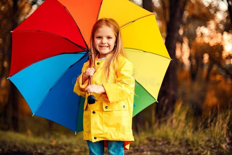 Rolig gullig litet barnflicka som bär det vattentäta laget med det färgrika paraplyet arkivfoton