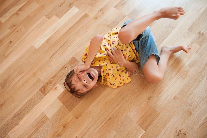 Rolig gullig pys i skjorta och kortslutningslögner på golv och skratt royaltyfri fotografi