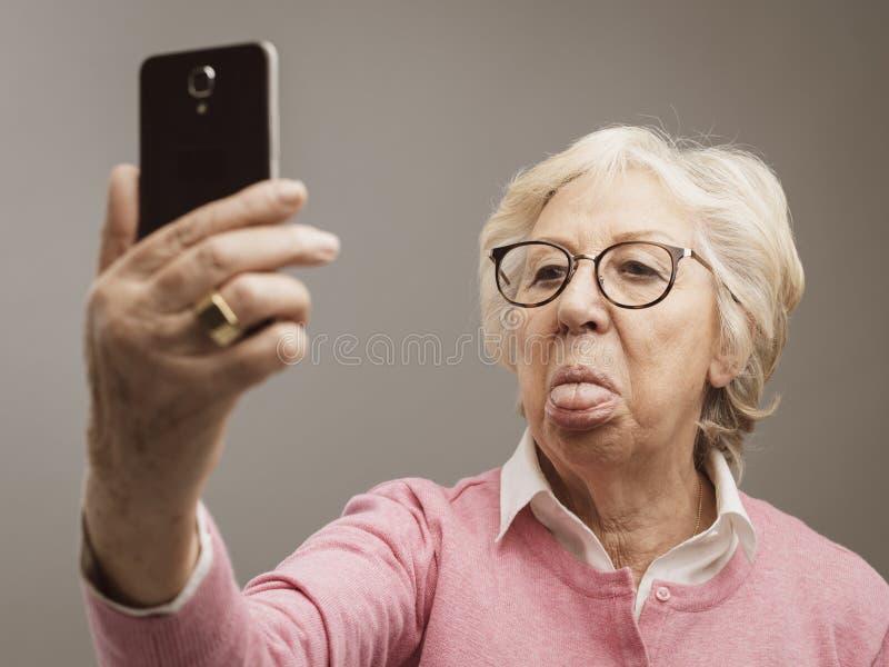Rolig hög dam som tar selfies med toungue ut arkivbilder