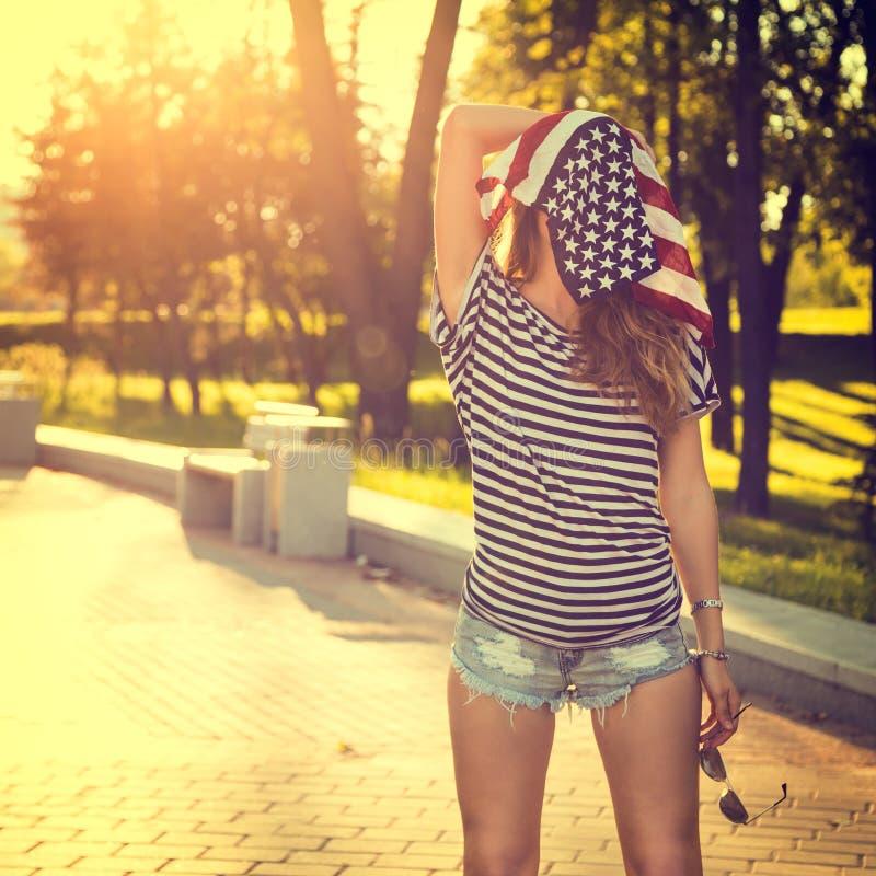 Rolig Hipsterflicka med USA flaggan på hennes huvud arkivfoto
