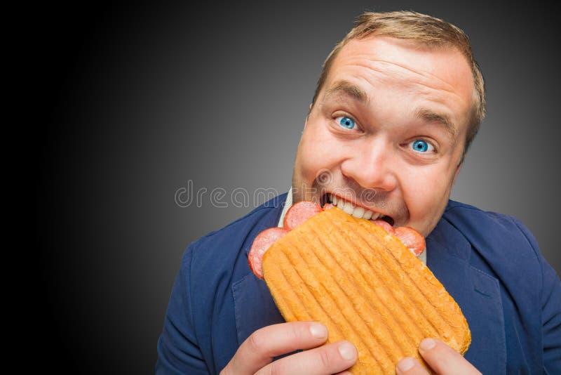 Rolig hungrig man som äter den smakliga smörgåsen royaltyfria bilder