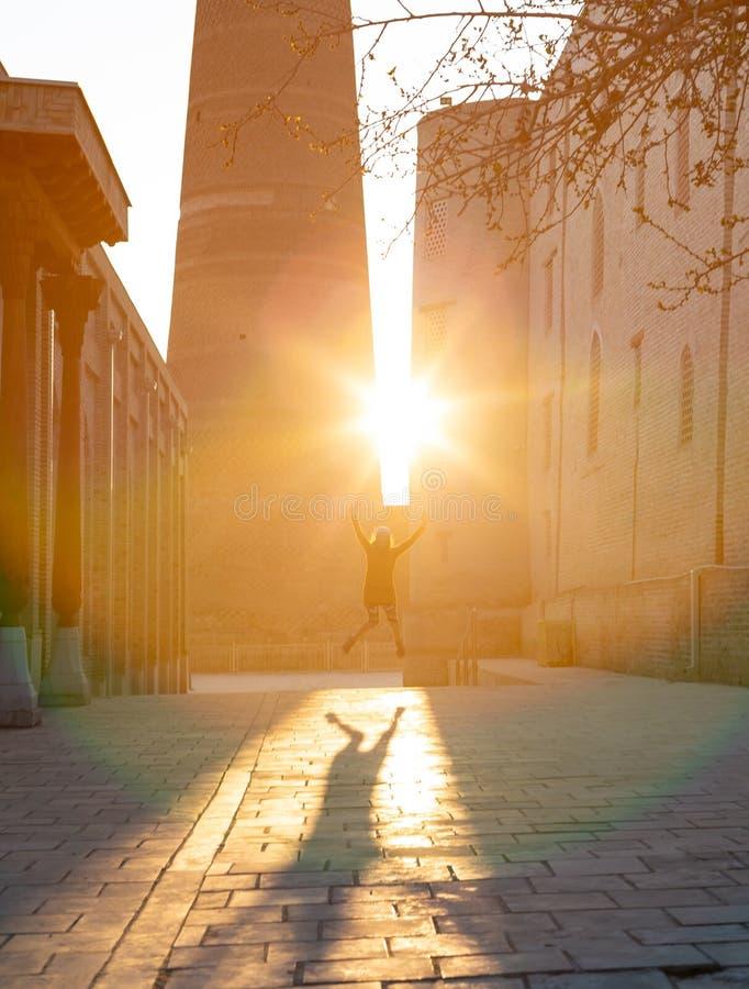 Rolig idérik ung flicka i grov bomullstvillhipsterkläder som hoppar upp mot solstrålar som gör stor skugga arkivfoto