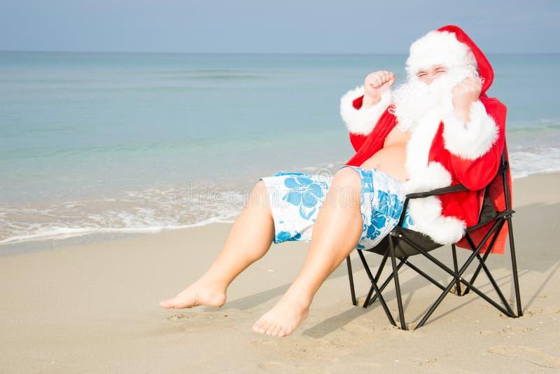 Rolig jultomten i kortslutningar på stranden royaltyfria foton