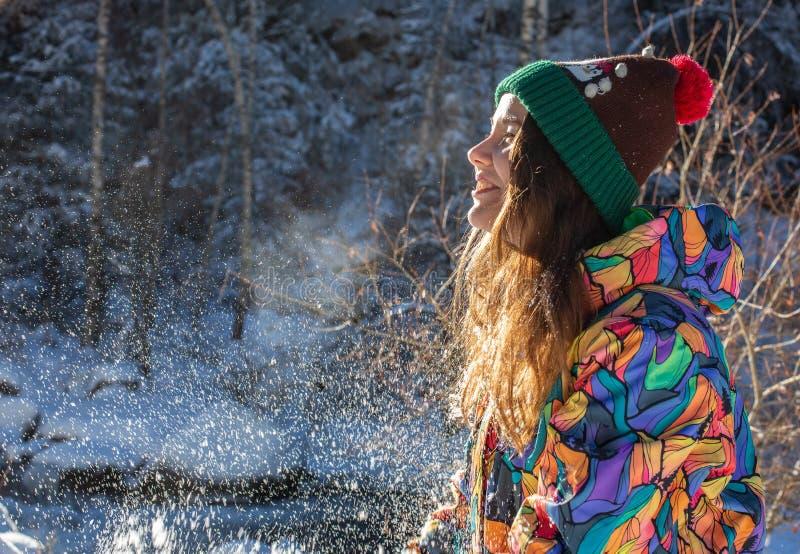 Rolig kvinna för lycklig vinter som kastar snöbanret Panoramaskörd av den utomhus- livsstilflickan som spelar i snö utanför att s royaltyfria bilder