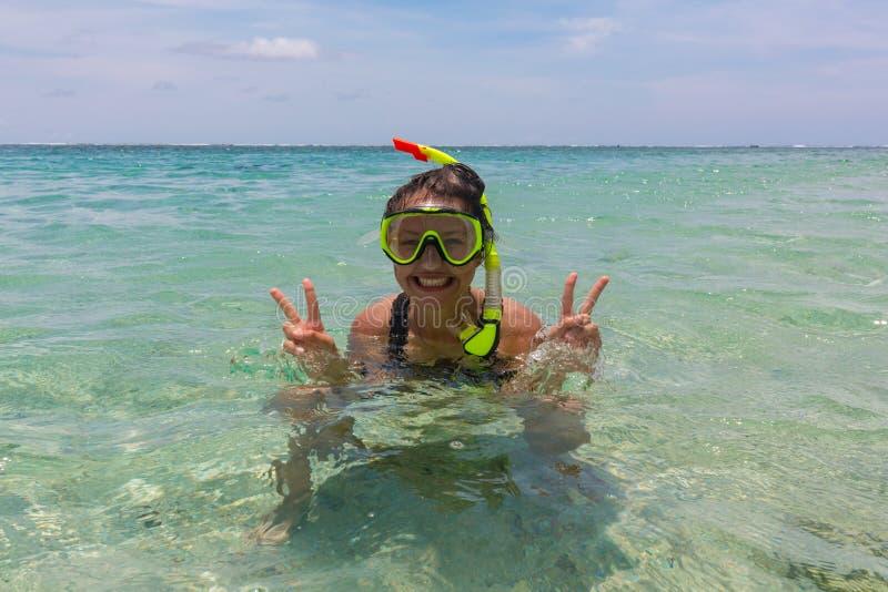 Rolig kvinna för strandsemester som bär en snorkeldykapparatmaskering som gör en fånig framsida, medan simma i havvatten closeup royaltyfri bild
