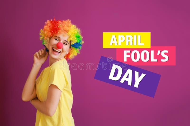 Rolig kvinna med partidekoren för April Fools \ 'dag på färgbakgrund royaltyfri fotografi